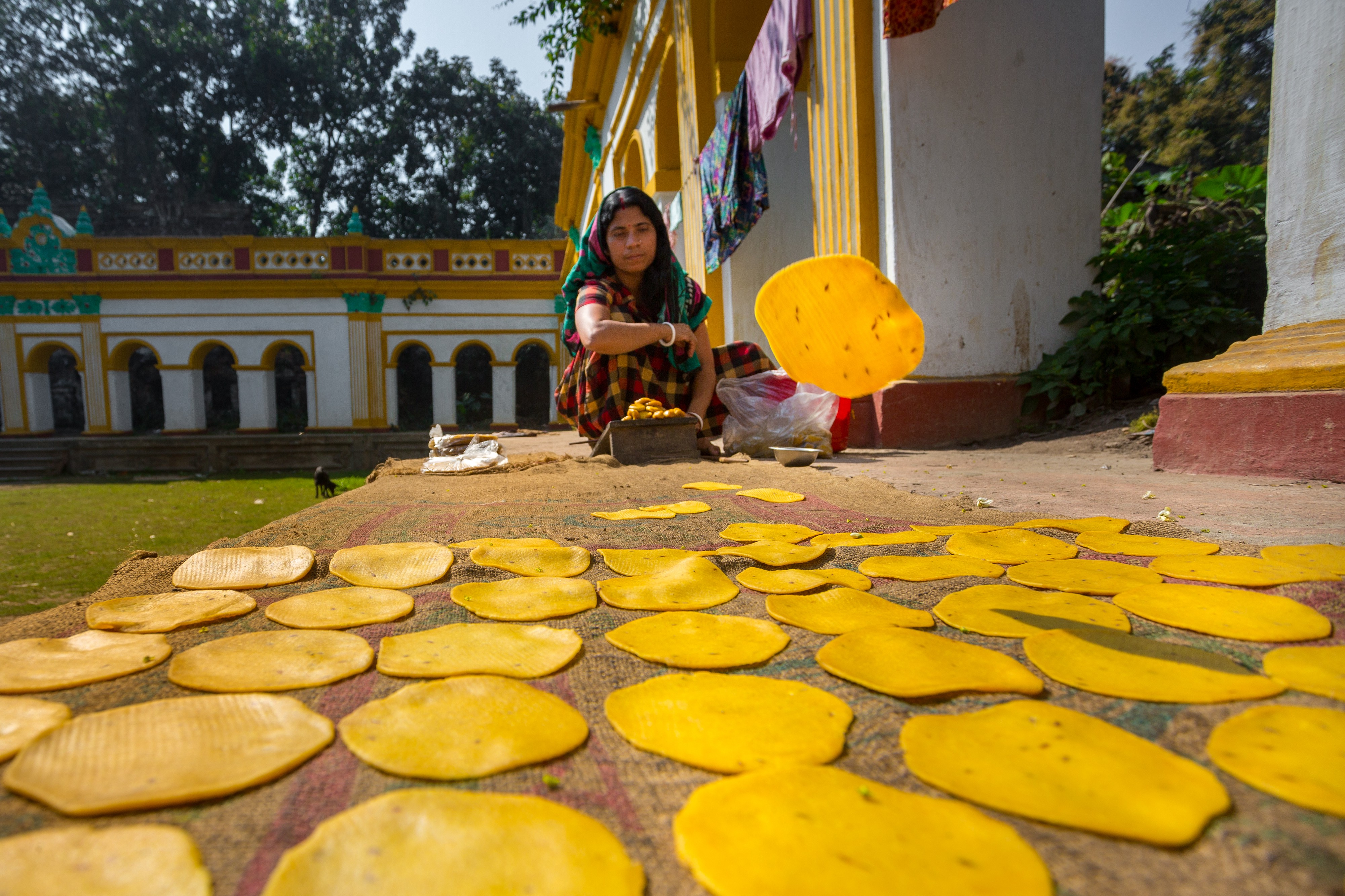 A small business woman making handmade Pappor (deep-fried bread) at Dinajpur Palace, Dinajpur, Bangladesh. Photo: © Jahangir