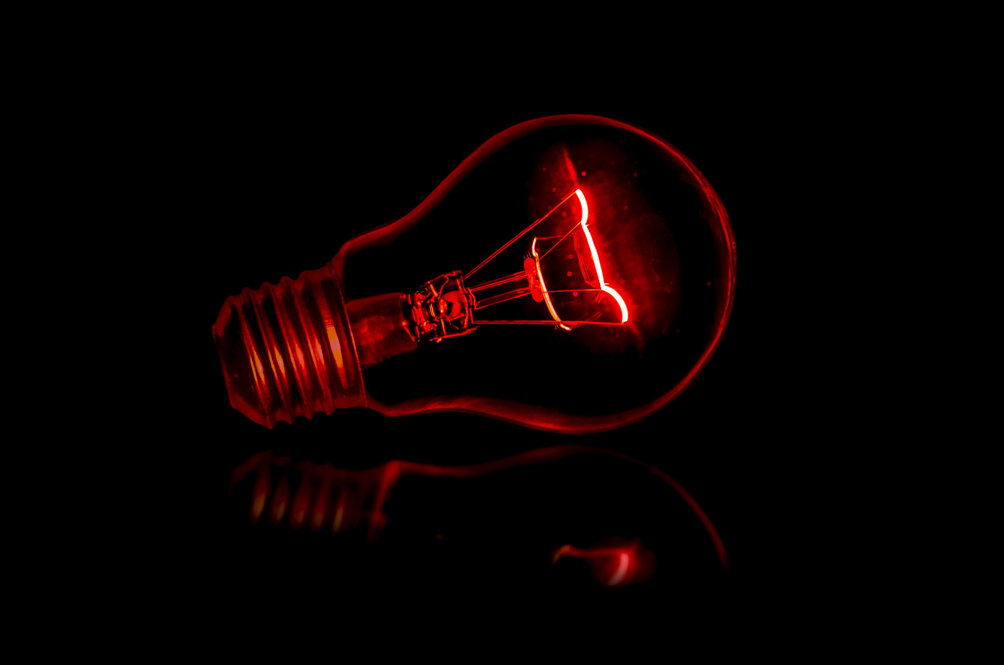 Photo of a lightbulb with red filament inside. by Terry Vlisidis.