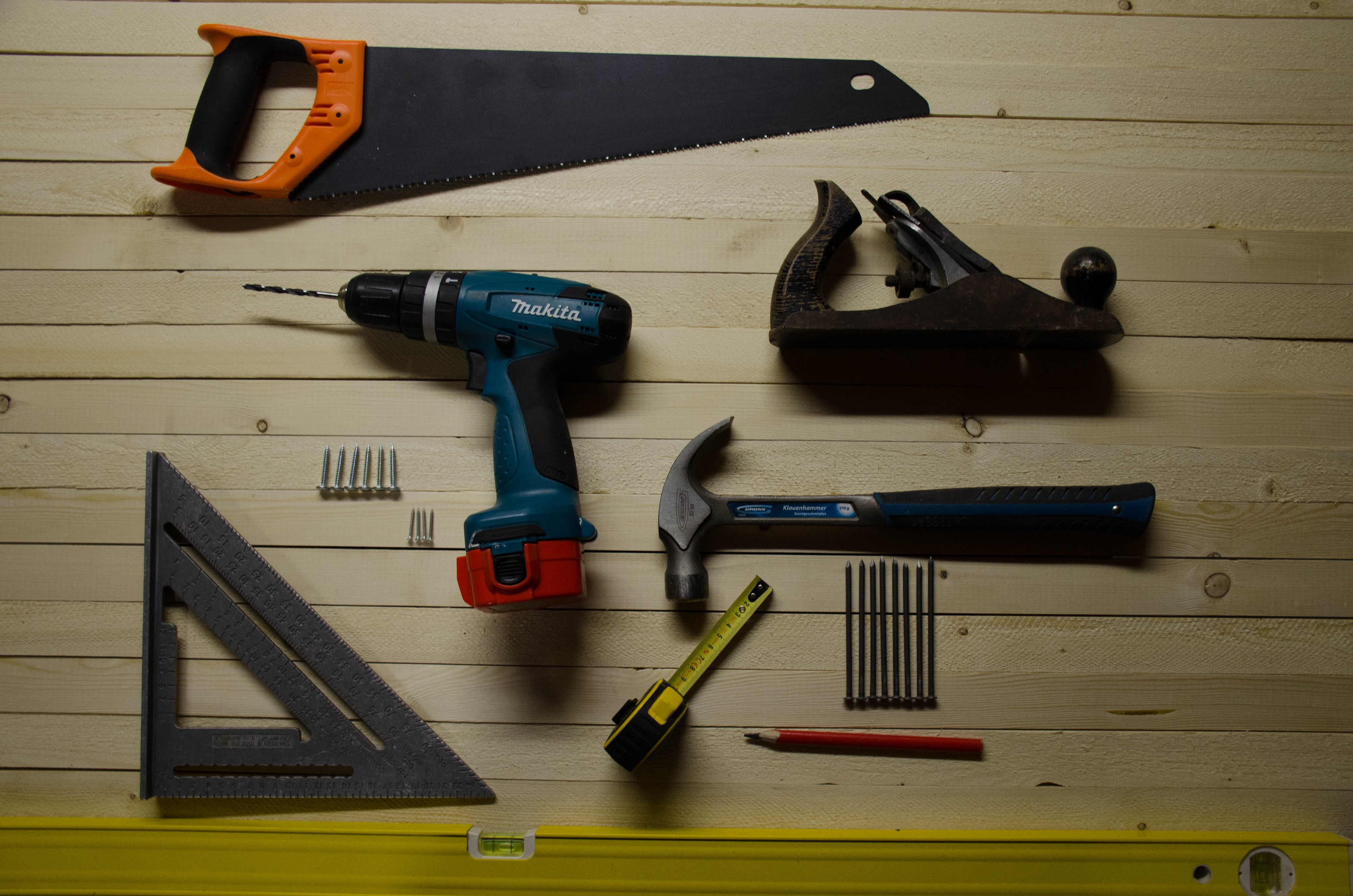 A hand saw, plane, hammer, nails, power drill, screws, tape measure, pencil, square and spirit level, neatly arranged.