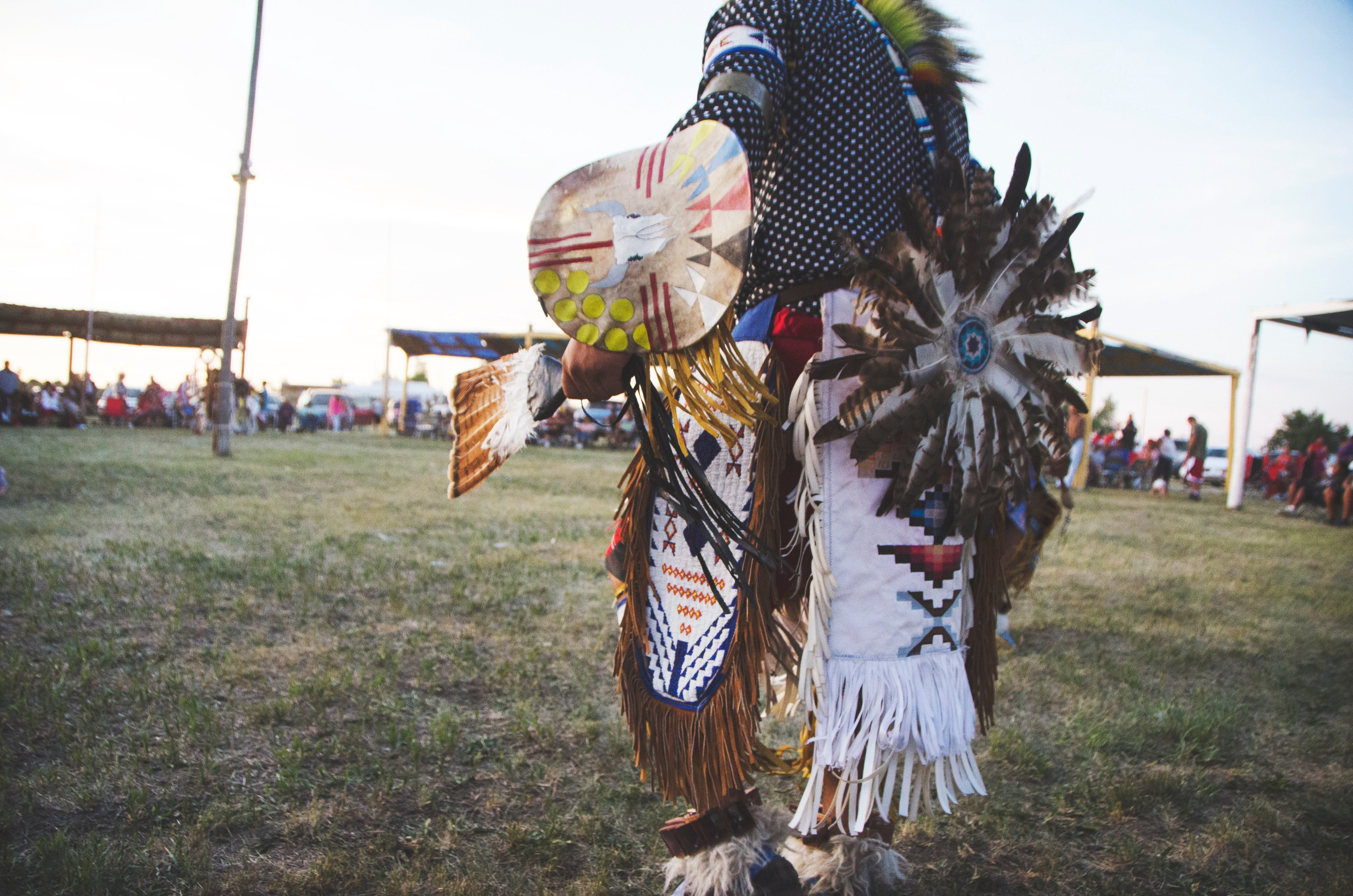 A Native American dancer seen partially from behind, wearing colorful PowWow regalia.