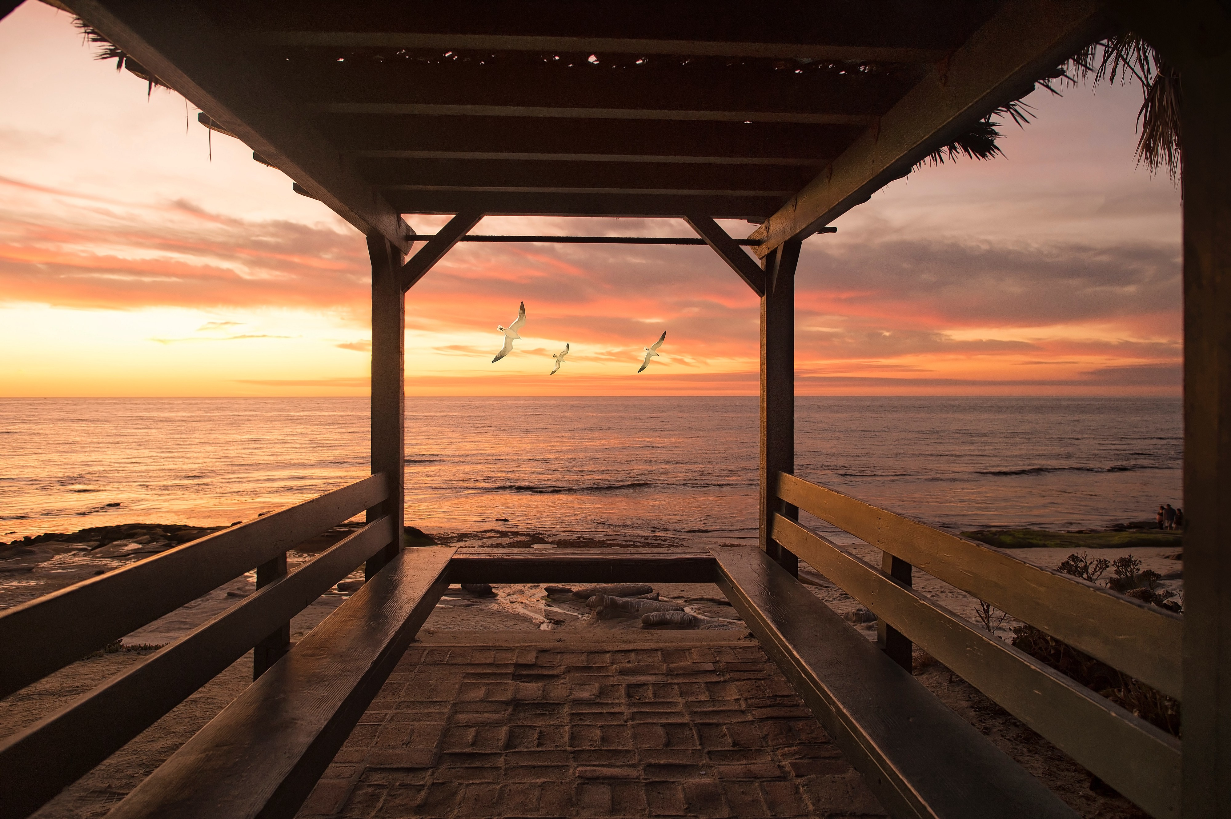 Gazebo bridge view towards a beach with a sunset background and birds flying.