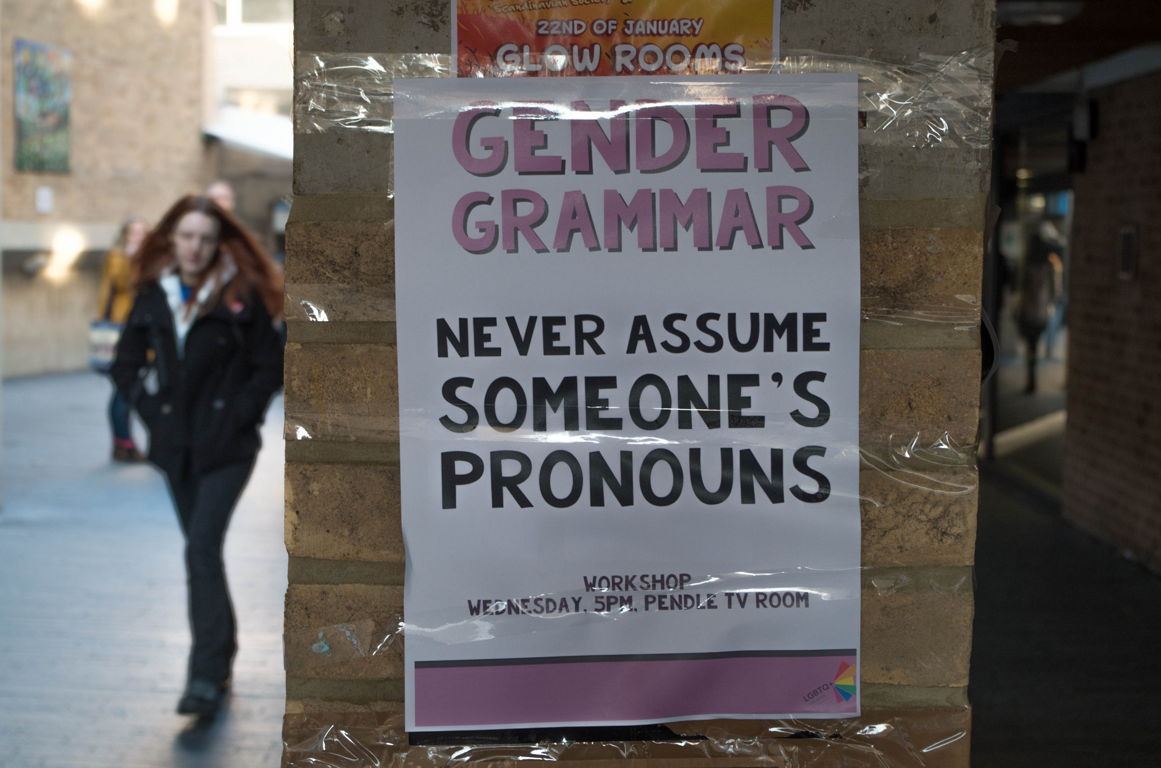 "Handmade poster taped to brick column, stating: ""Gender Grammar: Never Assume Someone's Pronouns."" Workshop Wednesday 5pm"