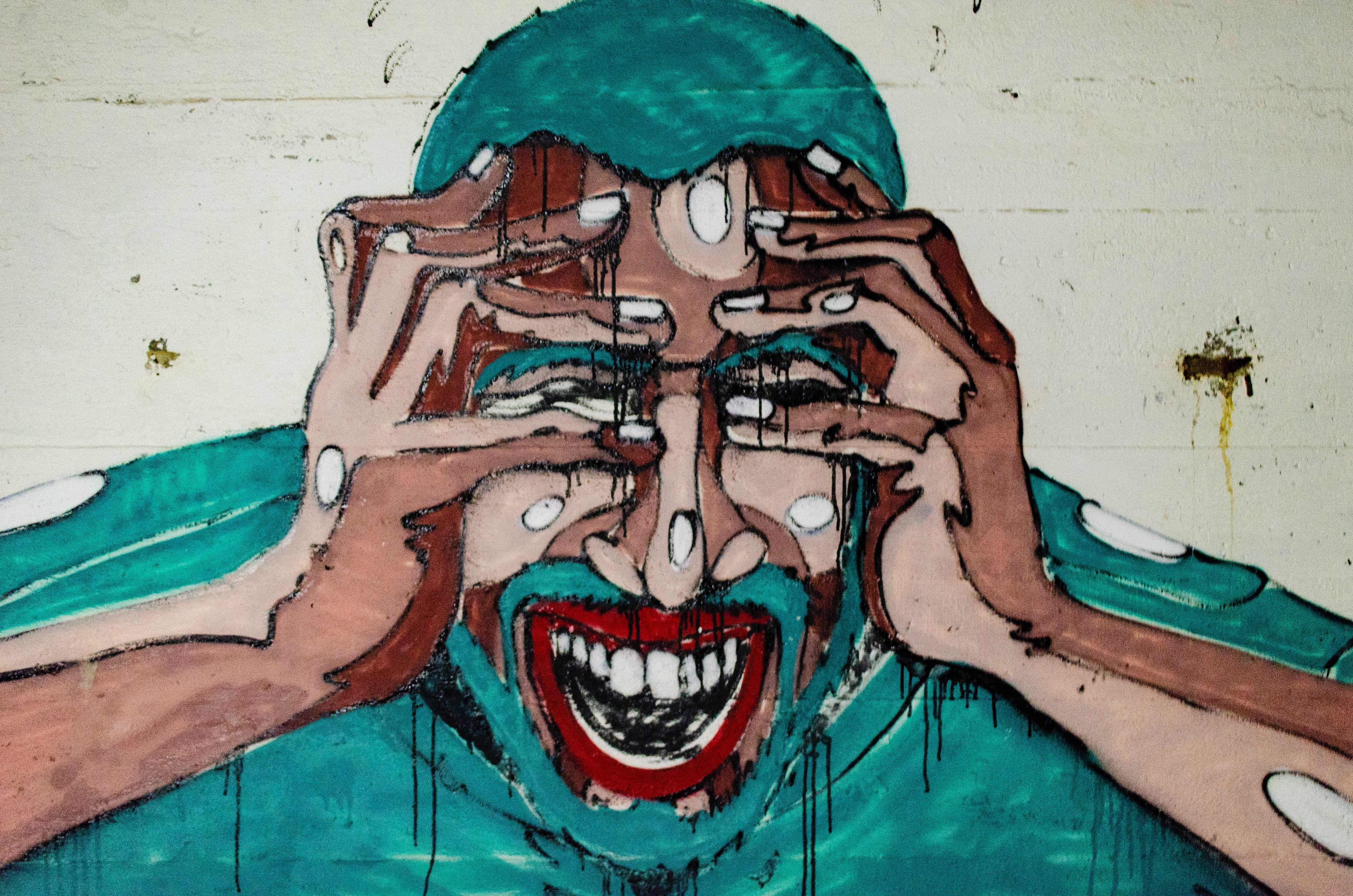 mural of a frightened, fearful man's face grimacing and holding his head