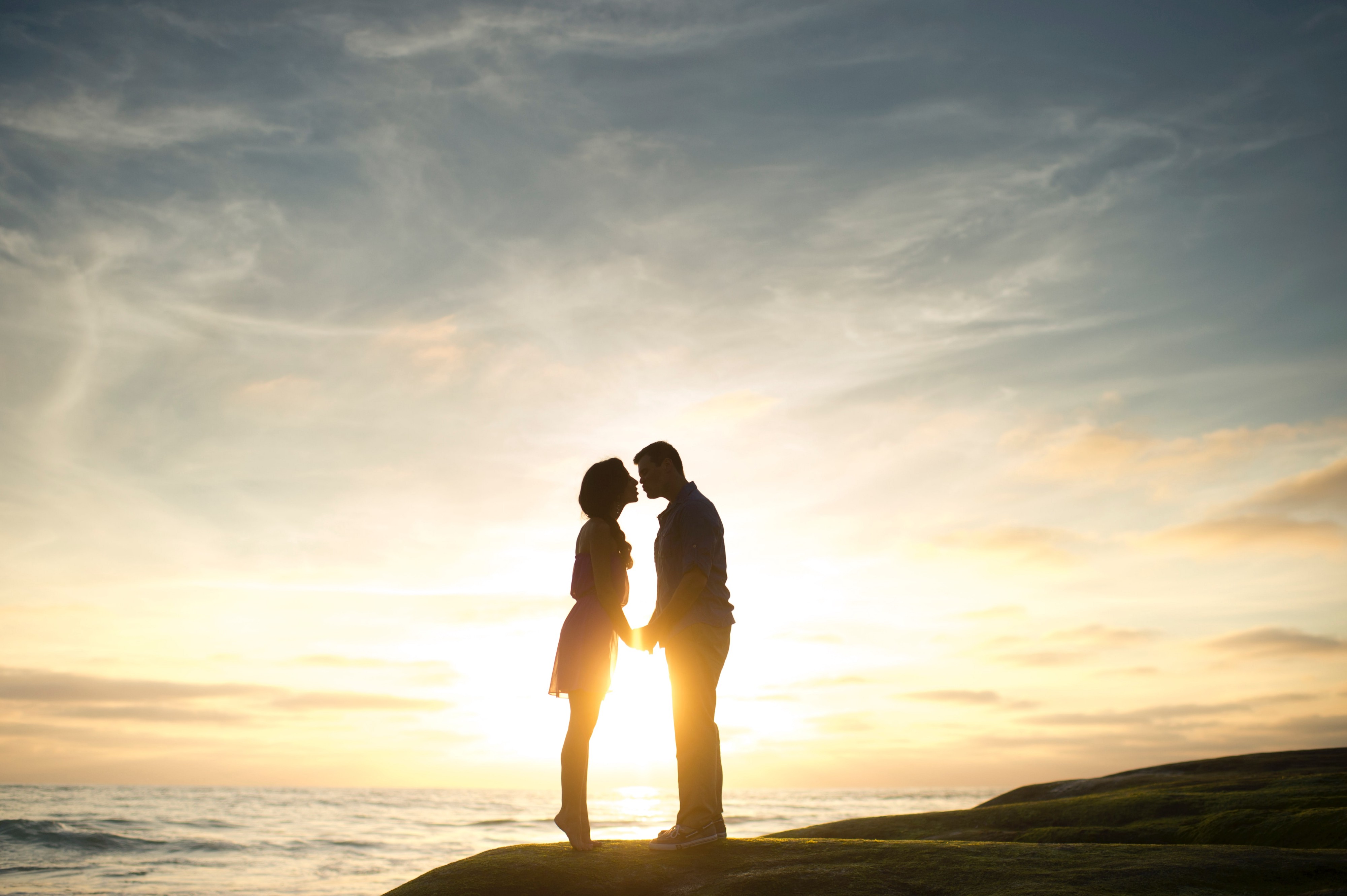 silhouette of man and woman facing each other holding hands on hill with sunset and ocean in background