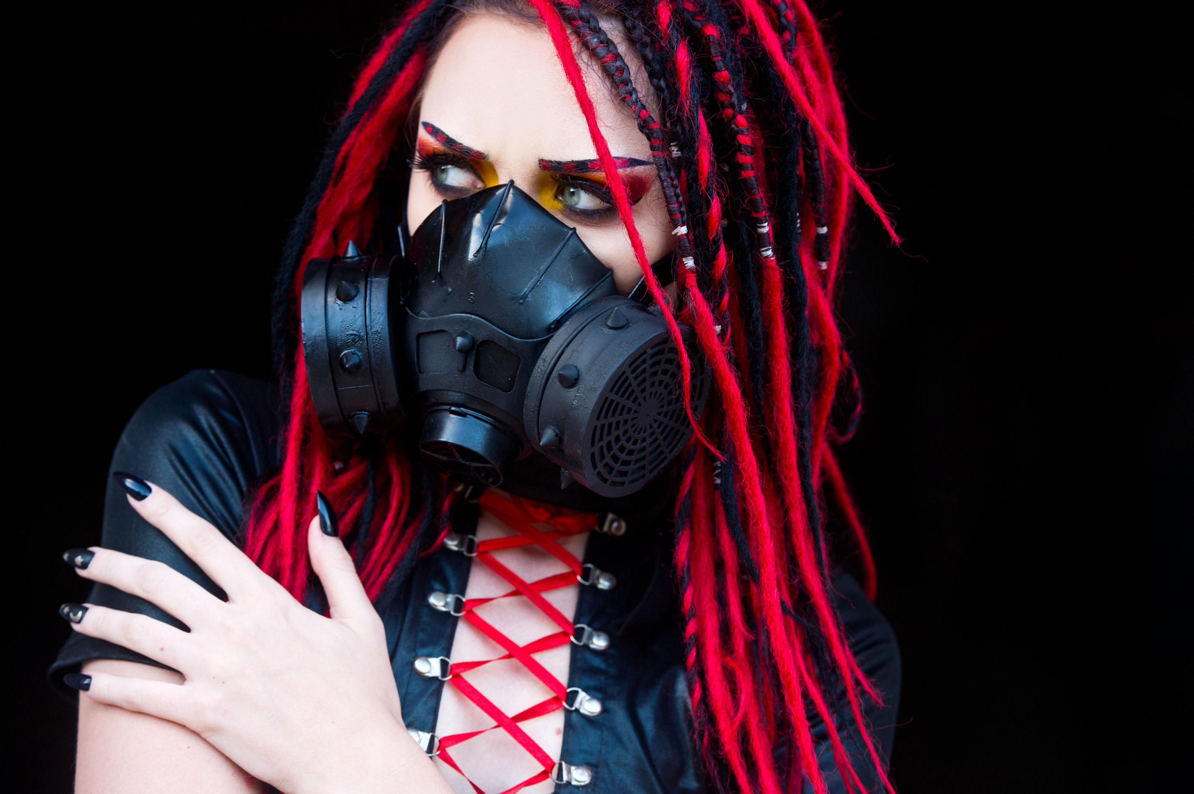 Young goth woman with bright red dreads and black spiked gas mask on black background staring camera-left