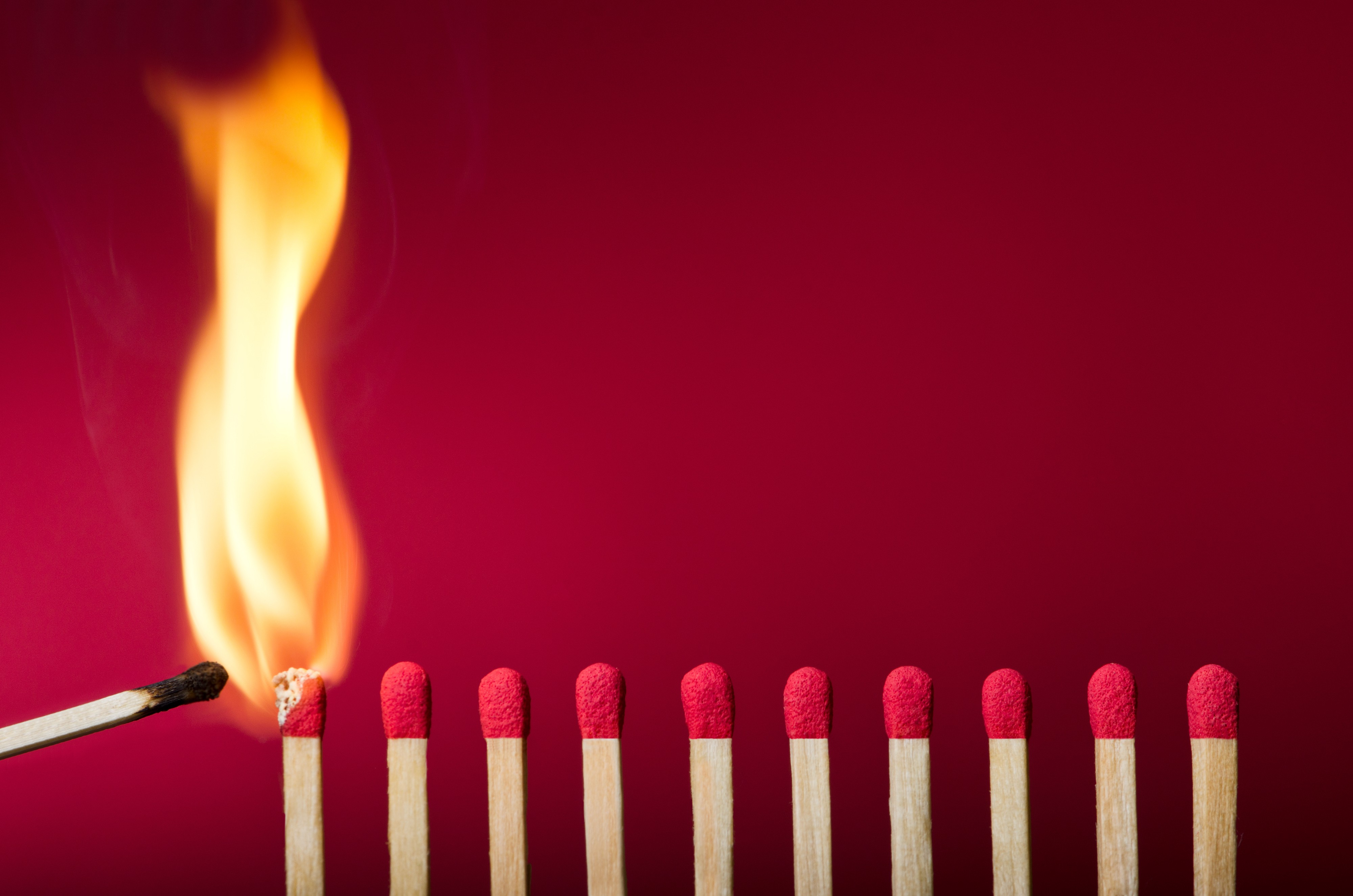 Row of closely spaced unlit wooden matches next to two that are burning against a red background