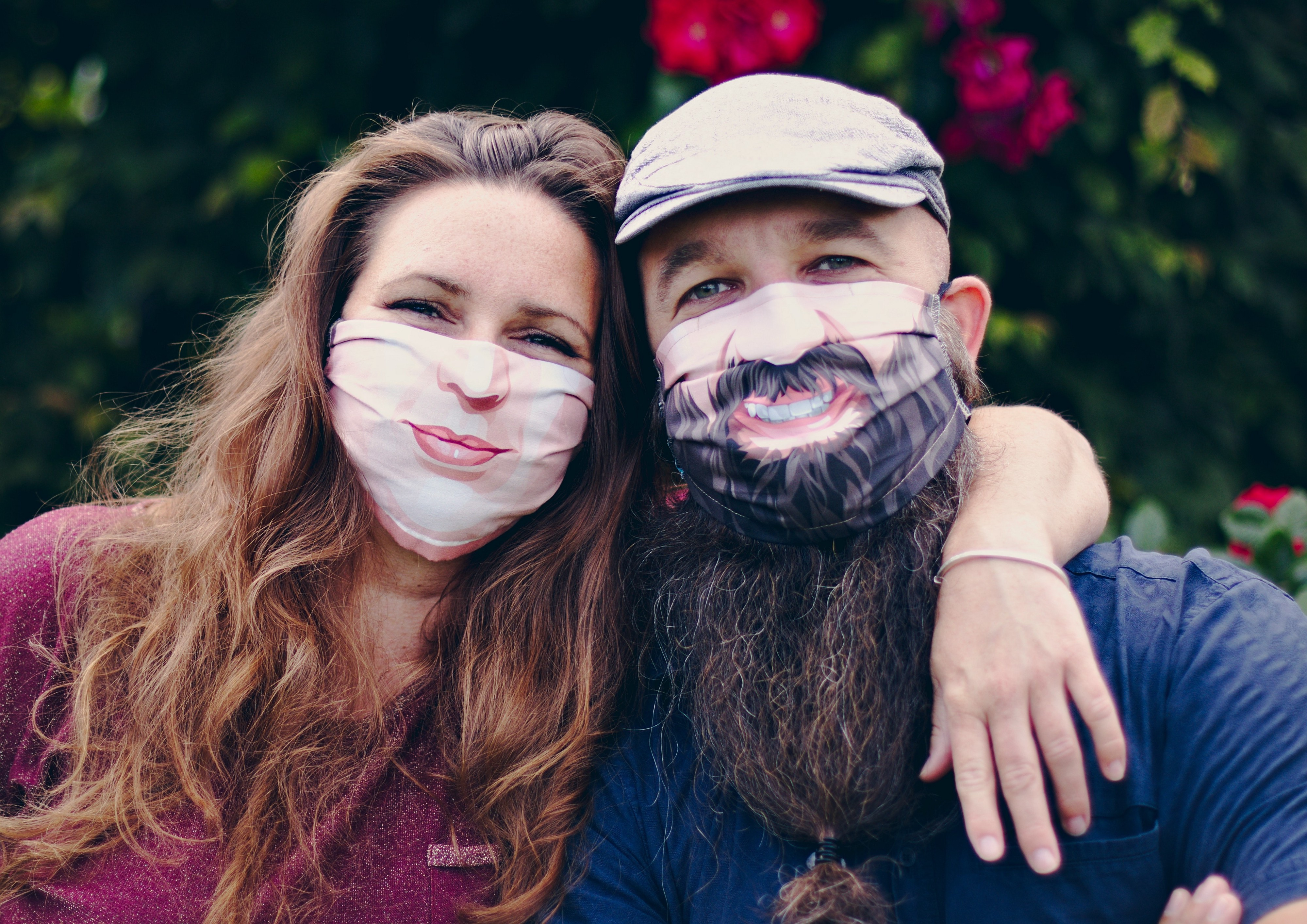 Couple poses in cloth face masks that have smiles printed on them.