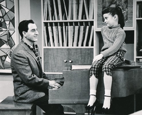 Danny Thomas plays piano for his daughter Linda, played by Angela Cartwright, seated on the piano.
