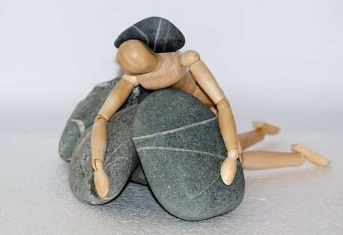A drawing figurine is draped over a pile of rocks and also has a rock on it's back.