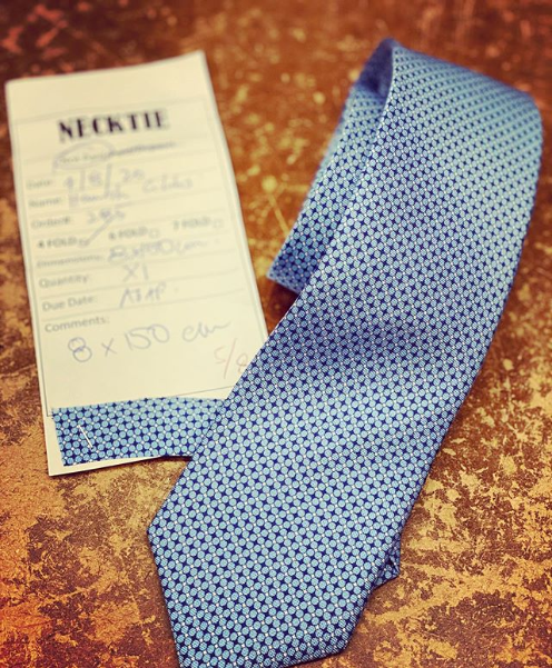 A gorgeous blue silk tie with the tailor's order and fabric sample rest on the cutting table of Rochefort Tailor, Sydney.