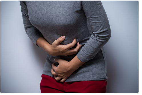Woman in grey sweater hunched over gripping her abdomen with both hands