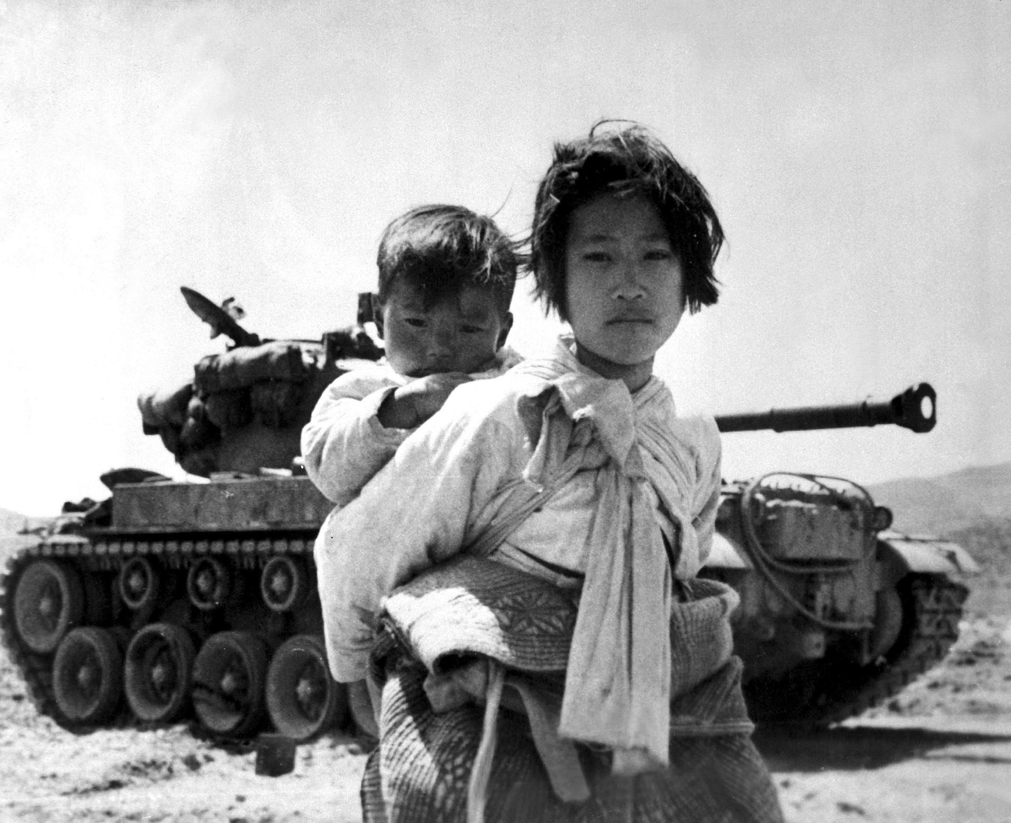 An archival photo from the Korean War. Carrying her baby brother on her back, a war weary Korean girl walks by a stalled M-26 tank, at Haengju, Korea, June, 1951.