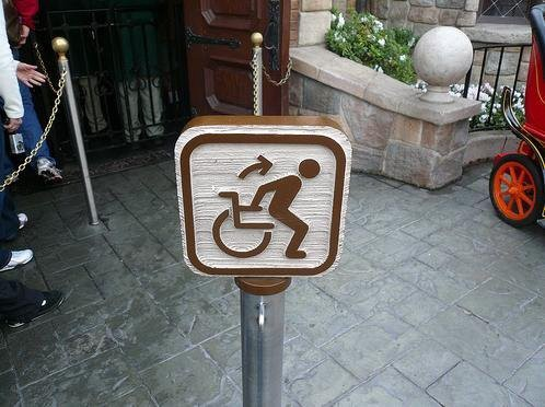 An erroneous wheelchair sign in disneyland depicts the user getting up out of it to get ready for a ride.