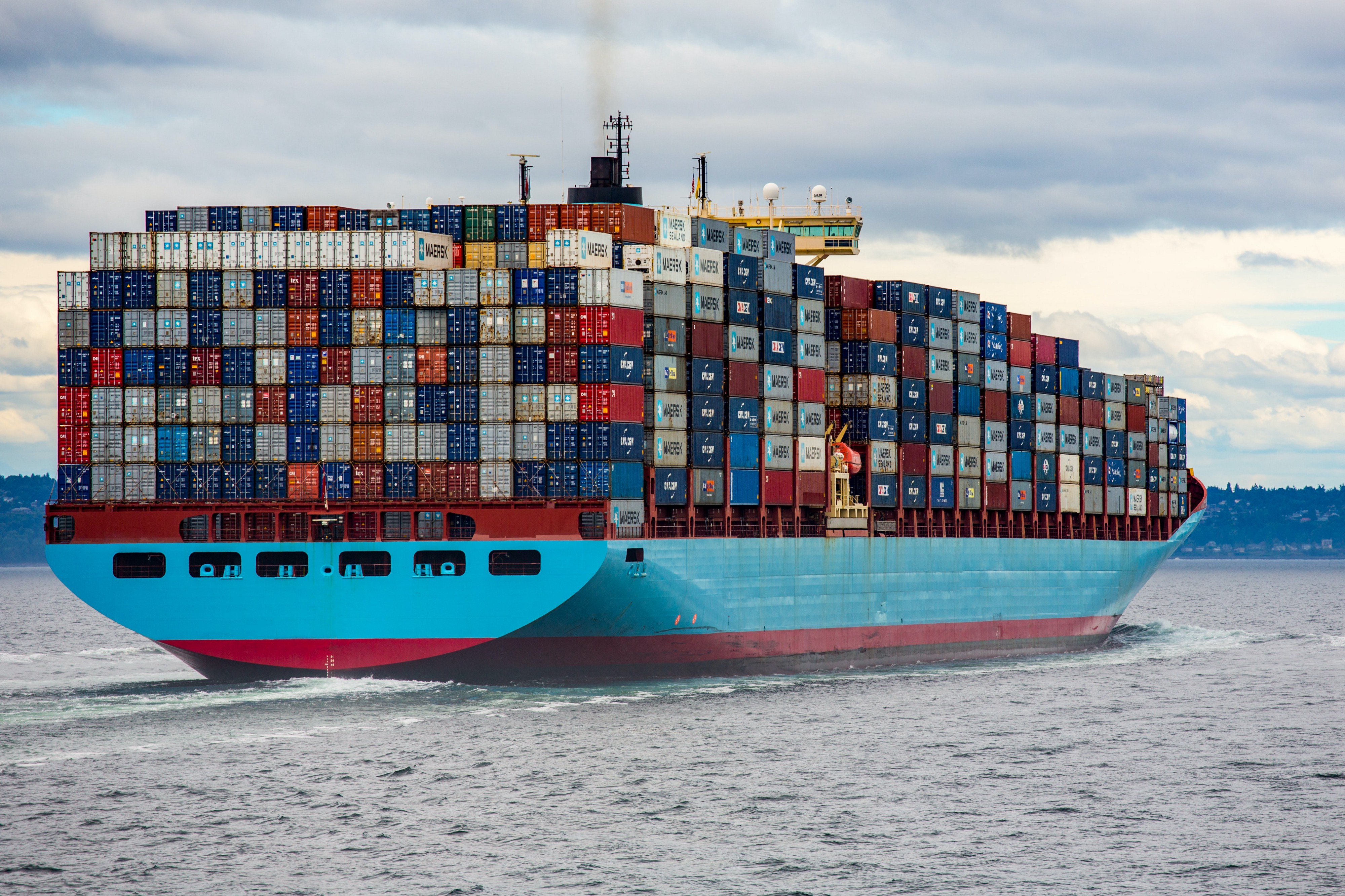A gigantic blue container ship stacked high with thousands of shipping containers on a body of water with hilly shore in the distance.