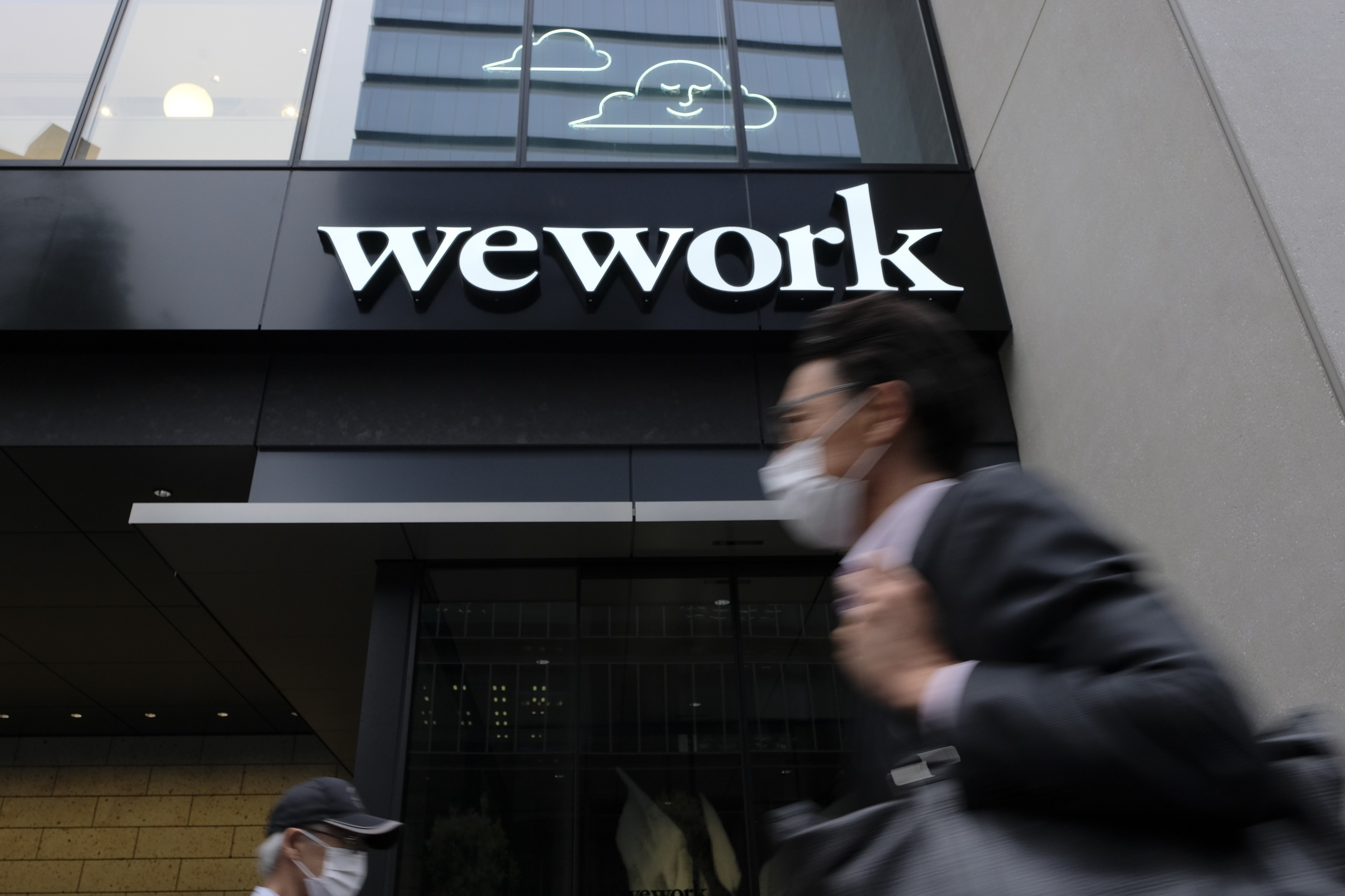 A man wearing a face mask walks past the front of a WeWork building in Tokyo.