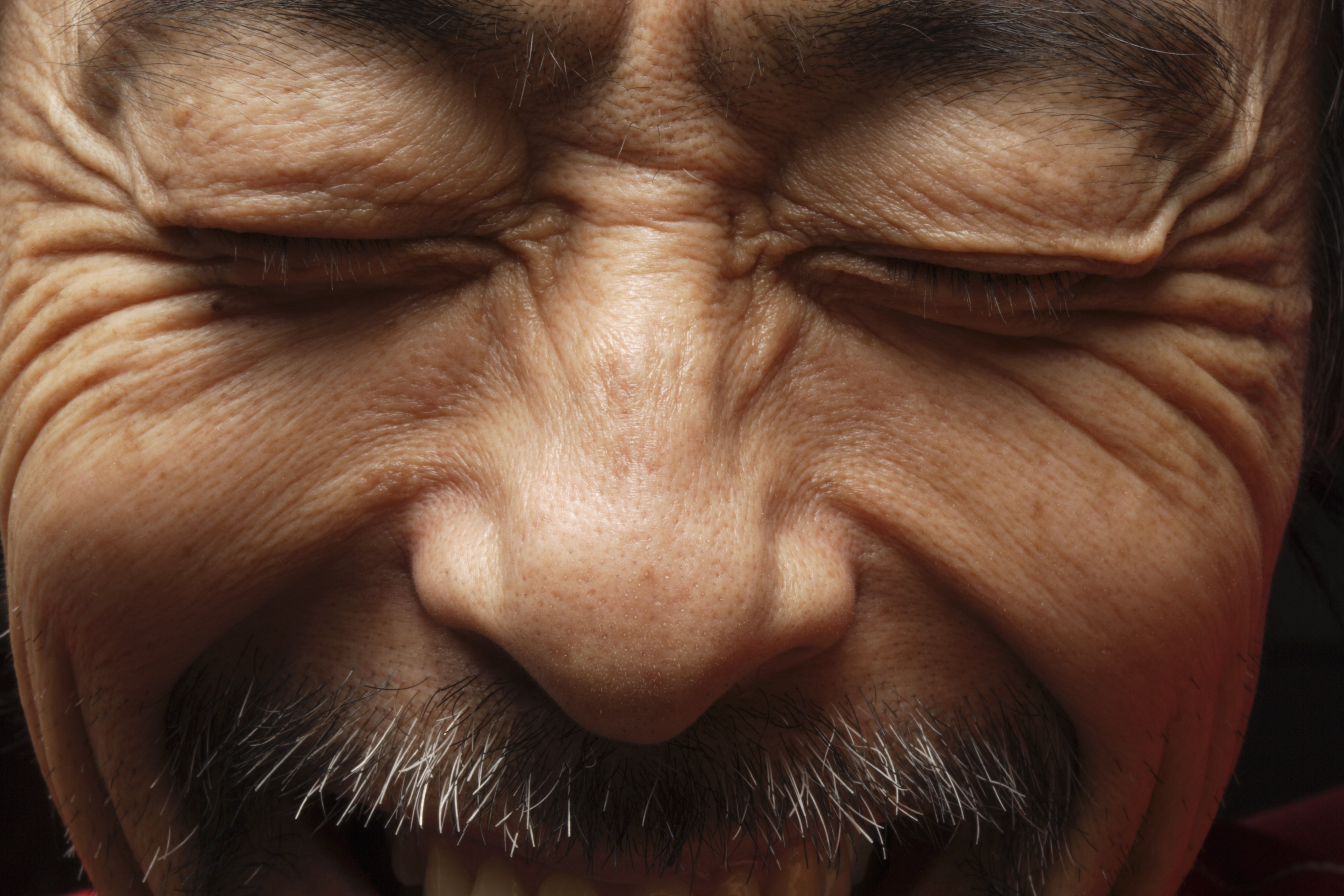 Close up of a man smiling with his eyes closed.