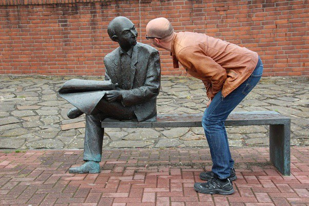 Man talking to sitting statue of another man in a bricked street scene