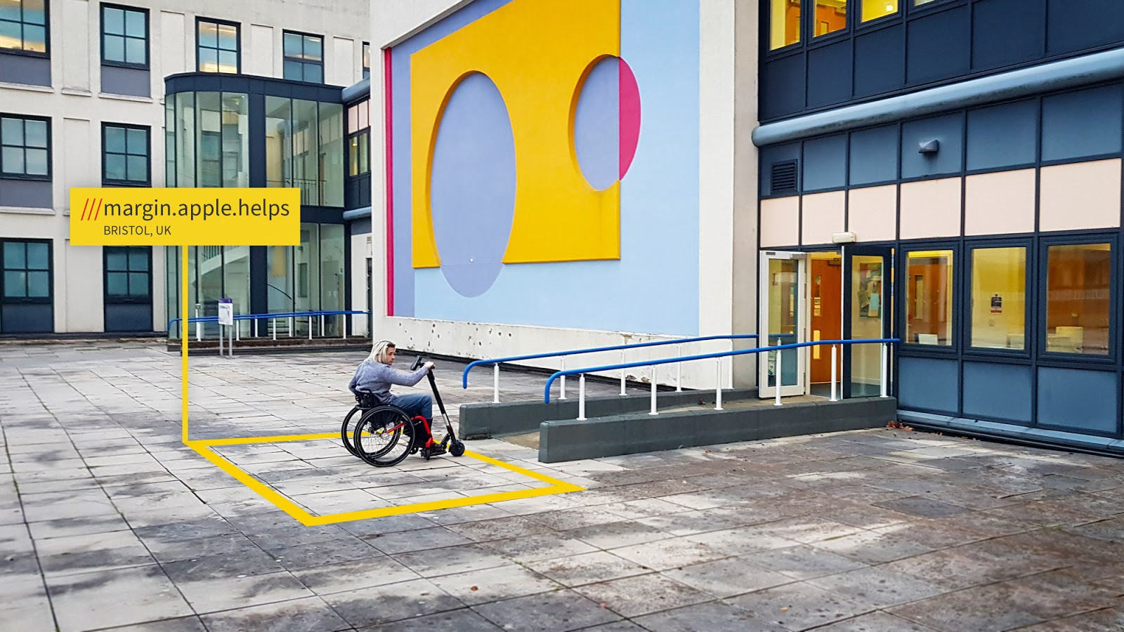 A person using a mobility scooter waits outside the accessible entrance of a colourful building in Bristol