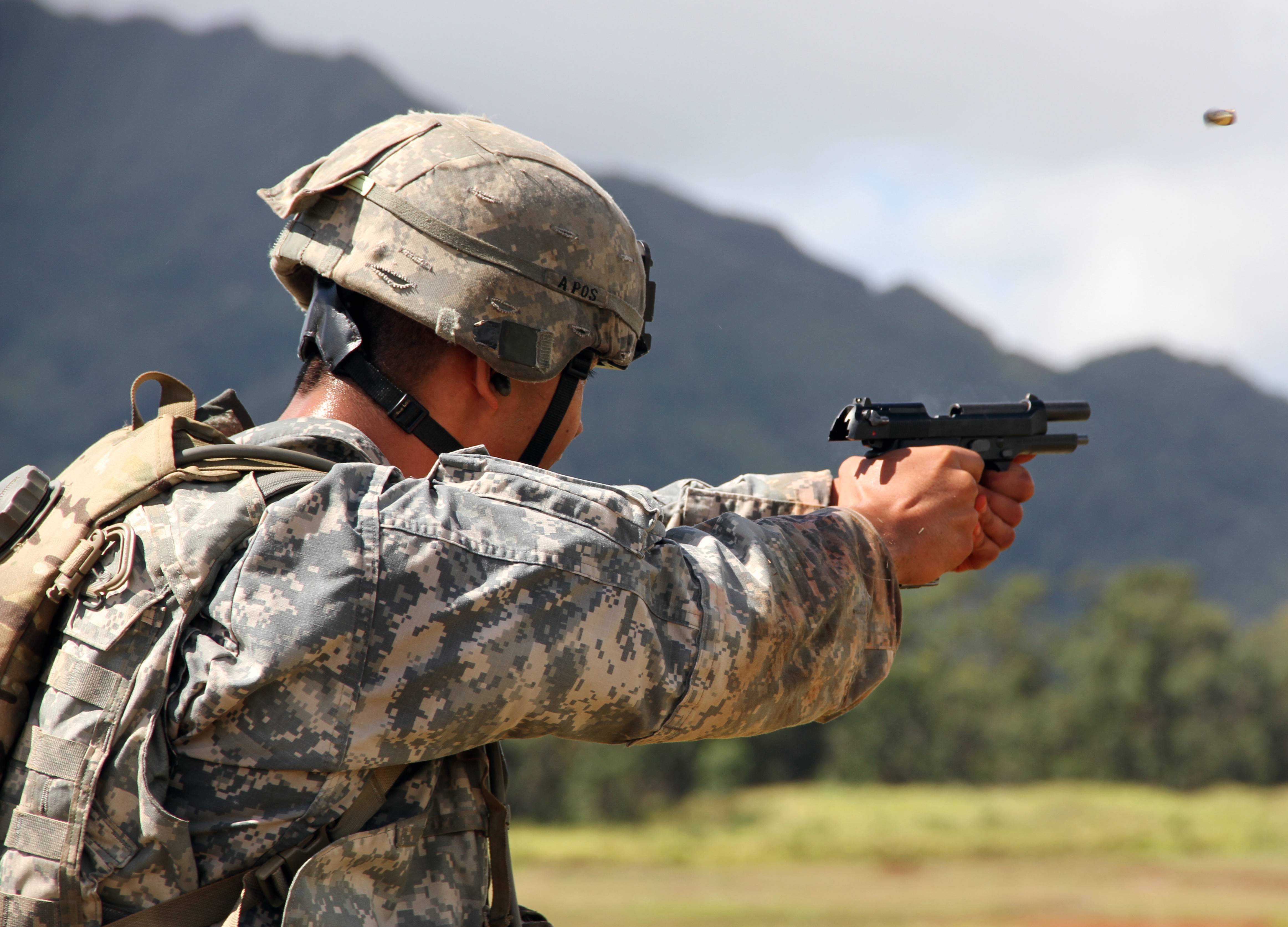 Above - a U.S. Army soldier shoots an M-9. At top - a Special Forces soldier takes part in a competition in Colombia with his Glock. Army photos