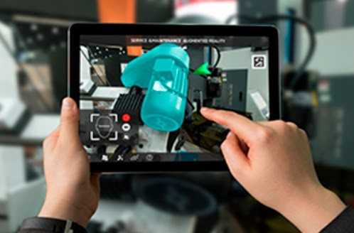 Mobile device shows in its screen instructions with the aid of Augmented Reality in the traditional industry, and hands are interacting with the screen.