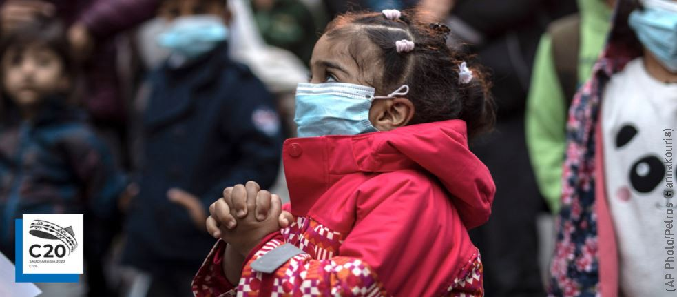 A young migrant girl, wearing a Covid-19 protection mask, is relocating from the overcrowded refugee camp on Lesbos Island to the Greek mainland, May 2020. (AP Photo/Petros Giannakouris)