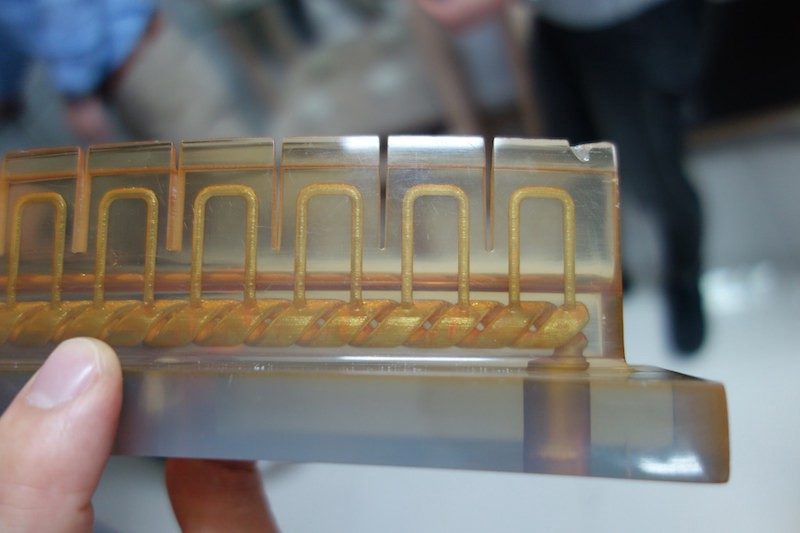 Innovative practices aren't just applied as a service, but also to in-house products. This photo shows how 3D printed molds can include cooling channels that will cool the final molded plastic piece 20% faster, which increases the production output significantly compared to traditional molding. Image: Peter Bihr (CC by-nc-sa)