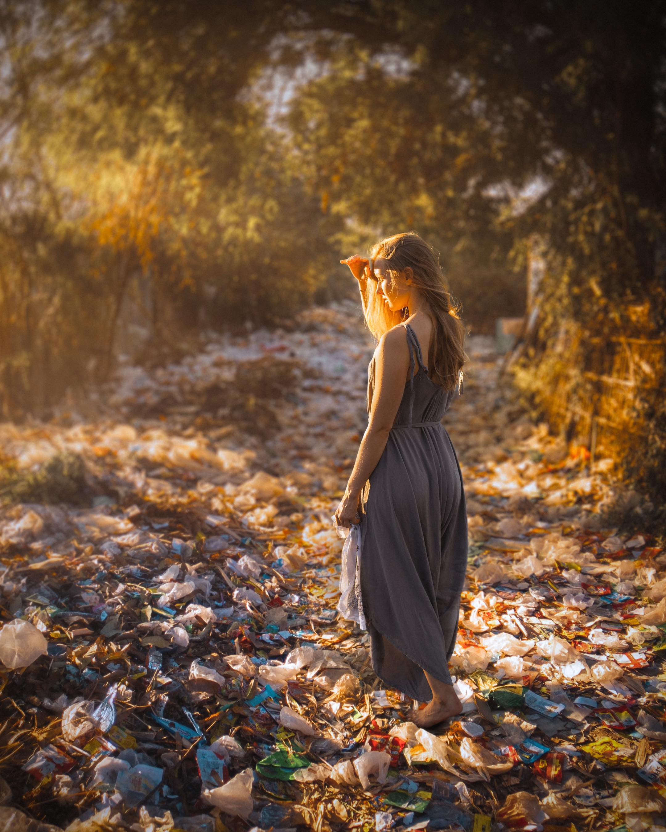A woman stands in a trash filled pathway that looks like fallen leaves at first glance