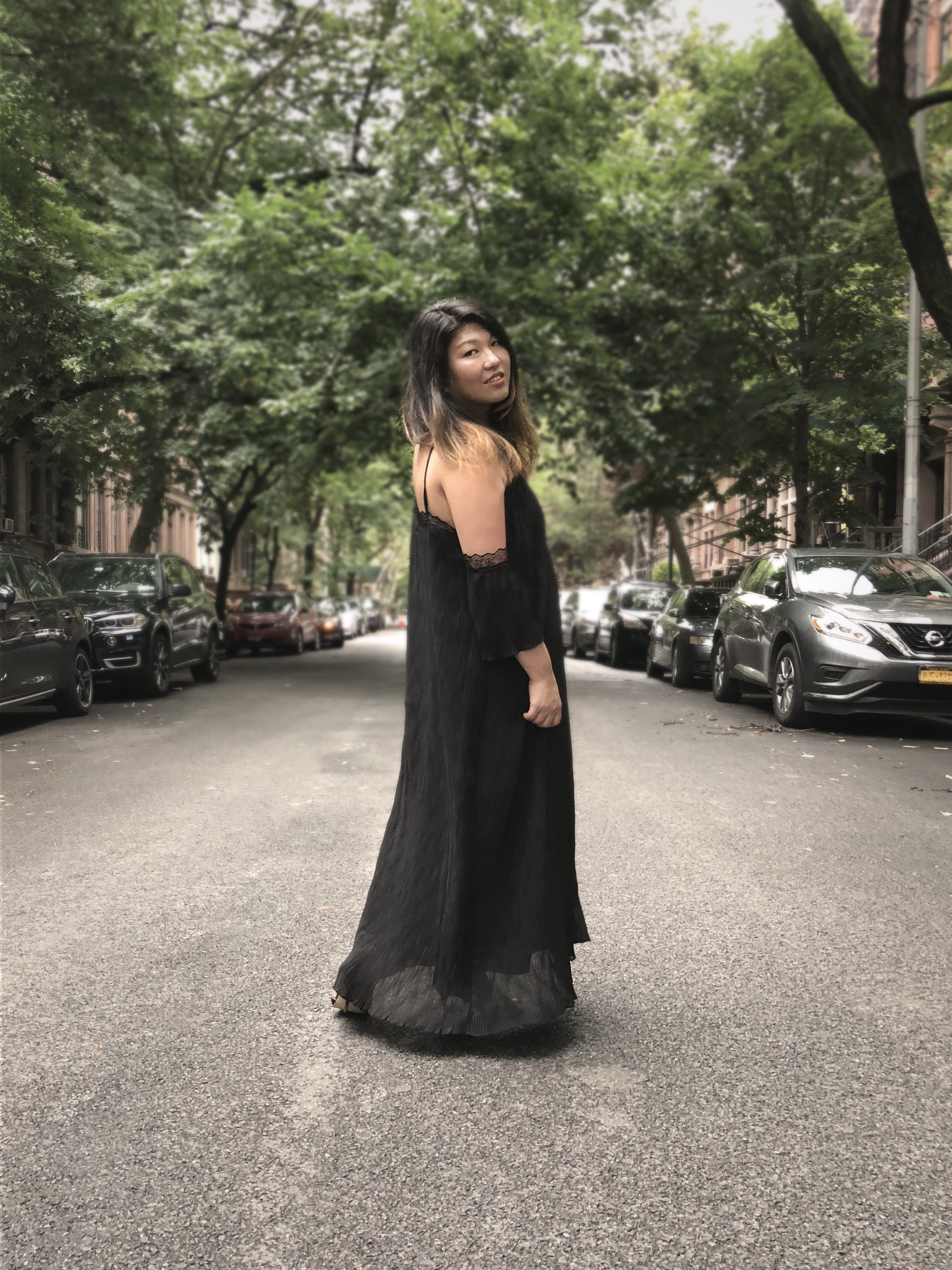Jolene Delisle, co-founder and creative director of The Working Assembly wearing the black pleated dress by Bastet Noir