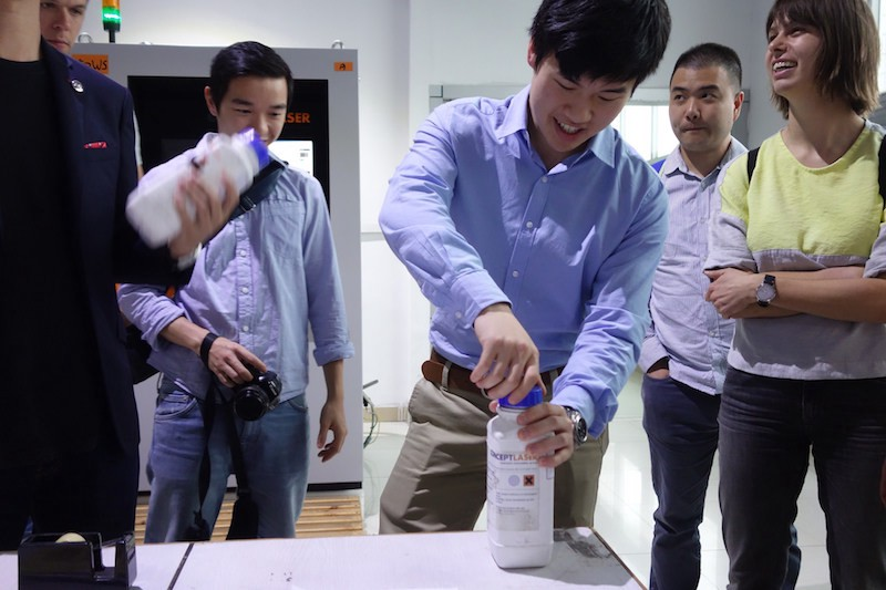 We get a demonstration of an industrial-grade 3D printer. The plastic bottle contains powder to print stainless steel. Image: Peter Bihr (CC by-na-sa)